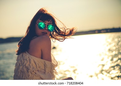 Beautiful styled girl at the beach during sunset
