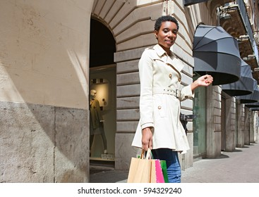 Beautiful stylish african american professional woman walking in expensive classic shopping street, carrying shopping bags in city, outdoors. Black female consumer, recreation lifestyle.