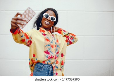 A beautiful and stylish black girl with long dark hair dressed in a yellow shirt and with sunglasses standing near wall in a summer city and use the phone