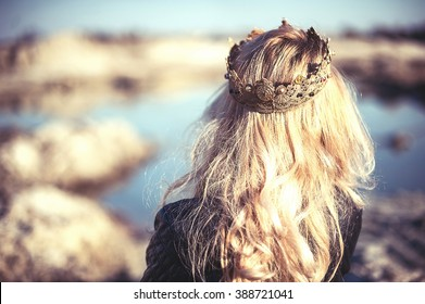 Beautiful stylish blonde girl with long wavy hair with a crown on the head walking near the lake or sea
