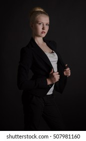 Beautiful stylish blonde woman in a severe black business suit