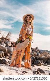 beautiful stylish boho model having fun  outdoors at sunset