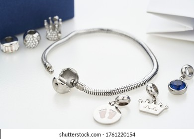 Beautiful stylish bracelet with silver charm beads with gems, isolated on white background. Assorted metal charm pendants for necklace or bracelet. Women accessories.
