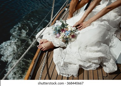 Beautiful stylish bride with a bouquet of hydrangeas and roses in the luxurious lace white dress on  yacht  board at sea