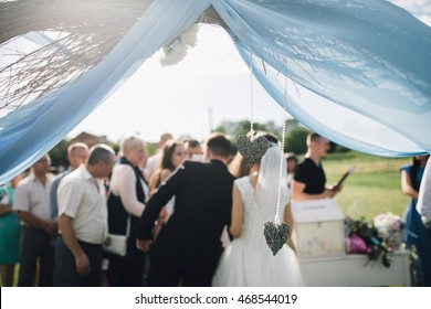 Beautiful stylish bride and groom under the wedding arch accept gifts and greetings from guests. Guests congratulate the newlyweds on their wedding day.