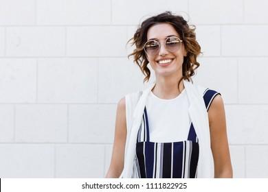Beautiful stylish Caucasian womam wearing sunglasses smiling and looking at camera.