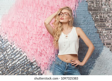 Beautiful stylish daring hussy blonde girl in stylish glasses, looks at camera and poses on abstract background