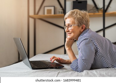 beautiful stylish elderly woman aged lies on the bed with a laptop