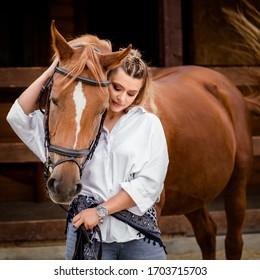 beautiful stylish fashion woman near horse on ranch. Fashion girl hugging a horse.