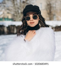 A beautiful, stylish, fashionable woman in a fur coat, hat and glasses, posing on the street in snowy weather.