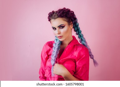 Beautiful stylish girl with colorful kanekalon braided in her hair. Pretty woman with colorful violet ombre hair and pro makeup isolated at pink background. Hairdresser salon concept