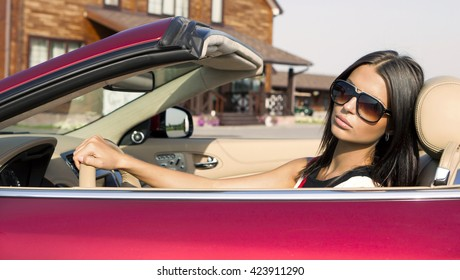 Beautiful stylish girl driving a powerful sports cabriolet