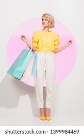 beautiful stylish girl holding colorful shopping bags and posing on white with pink circle