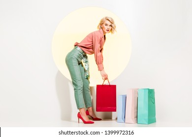 beautiful stylish girl holding shopping bag and looking at camera on white with yellow circle
