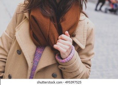 Beautiful stylish girl with long dark hair in a brown wool scarf on a cold winter day, street fashion, winter outfit