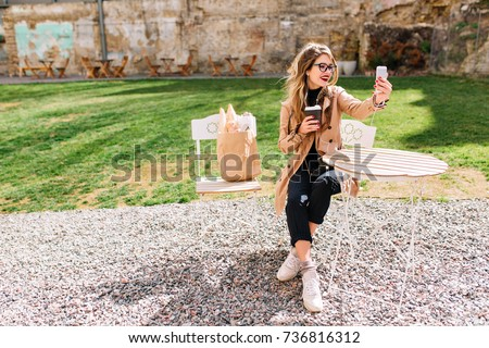 Beautiful stylish girl with long hair makes a video call on the phone while drinks latte in outdoor cafe. Charming female blogger is videotaping for youtube while sitting in the park after shopping.