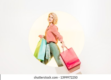 beautiful stylish girl looking at camera and holding shopping bags on white with yellow circle
