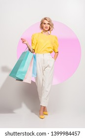 beautiful stylish girl looking at camera and holding colorful shopping bags on white with pink circle