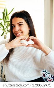 Beautiful stylish girl making heart shape with hands.