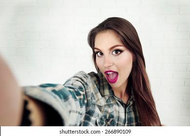 Beautiful stylish girl making selfie on brick wall background
