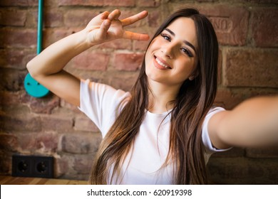 Beautiful stylish girl making selfie with victory gesture