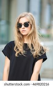 Beautiful stylish girl on blurred street background