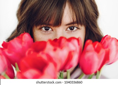 beautiful stylish girl with pink tulips on white background. sensual looking eyes of young woman and flowers. natural beauty. skin care. spring bride bouquet. happy womens day