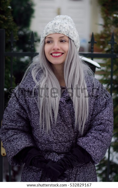 Beautiful stylish girl in pom pom hat with wine red lips and grey hair walking in the city in winter
