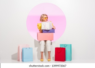 beautiful stylish girl posing with colorful gift boxes and shopping bags on white with pink circle