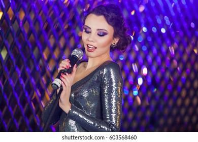 Beautiful stylish girl in shiny black evening dress singing at the Night club