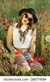 Beautiful stylish girl in a summer field