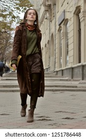 Beautiful stylish girl walking on the sidewalk on the background of historic buildings. She is dressed in a boho style: brown coat, yellow bag, green sweater.