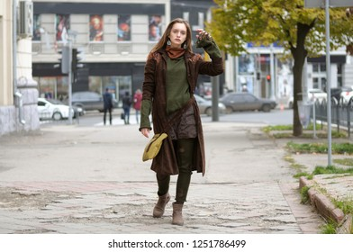 Beautiful stylish girl walks on the broken sidewalk. She is dressed in a boho style: brown coat, yellow bag, green sweater, shorts and torn stockings