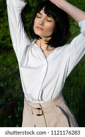 Beautiful stylish girl wearing a trendy white shirt, beige trousers and a black wig posing relaxing outdoors in sunlight in green meadow. Advertising and fashion design. Copy space.
