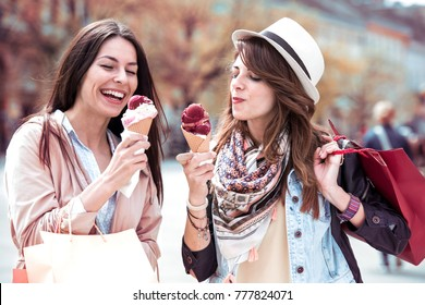 Beautiful stylish girls is eating ice cream, talking and smiling while walking after shopping.