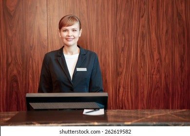 Beautiful stylish hotel receptionist standing behind the service desk in a hotel lobby looking at a guest with a friendly smile