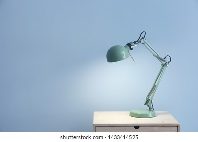 Beautiful stylish lamp on table against color background