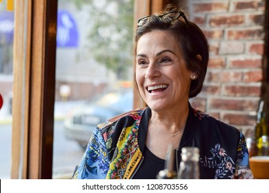 Beautiful and stylish middle aged woman laughing at a restaurant with her friends