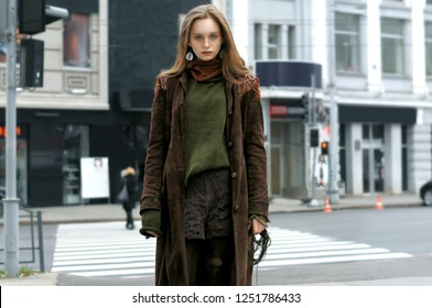 Beautiful stylish model posing against a pedestrian crossing and modern buildings. She is dressed in a boho style: brown coat, green sweater, shorts and torn stockings