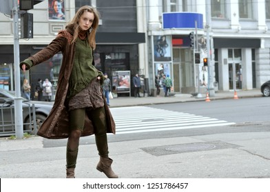 Beautiful stylish model is spinning on the background of a pedestrian crossing and modern buildings. She is dressed in a boho style: brown coat, green sweater, shorts and torn stockings