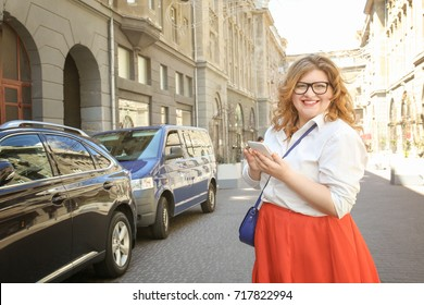 Beautiful stylish overweight woman with mobile phone outdoors