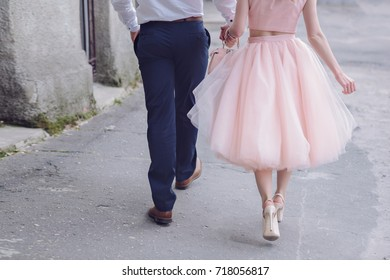 Beautiful stylish pair of European looks A young lovers couple walks holding hands Girl in a tutu dress with hugging her groom A couple walks through the streets of the city