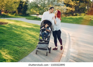 beautiful and stylish redhead mom in a white blouse wallking with her beautiful man dressed in a white shirt and blue jeans and they carry their little son in a cart