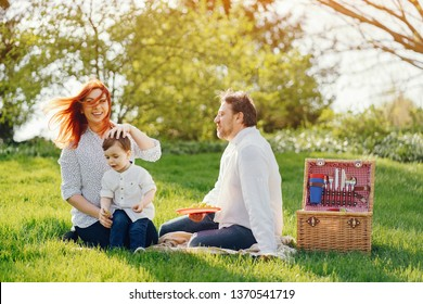 beautiful and stylish redhead mom in a white blouse sits on the grass with her beautiful man dressed in a white shirt and blue jeans; they play with their little sweet son who eats grapes