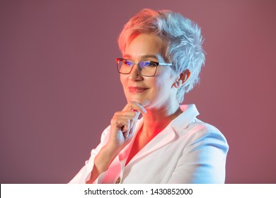 beautiful stylish woman aged, wearing glasses, in a white jacket on a pink background