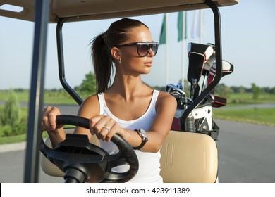 Beautiful stylish woman driving a golf car