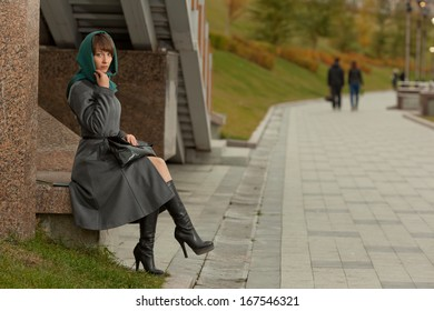Beautiful stylish woman  in grey coat sitting and thinking outdoors