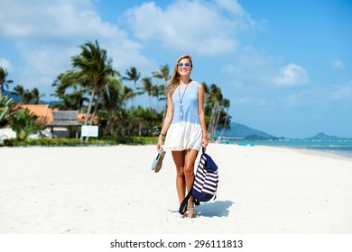 Beautiful stylish woman having fun and standing on the beach in summer blue sky and white sand
