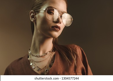 beautiful stylish woman posing in trendy glasses isolated on brown