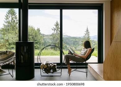 Beautiful stylish woman reading book on chair at fireplace with firewood on background of mountain hills. Young female in casual clothes relaxing in modern chalet with amazing view from window - Shutterstock ID 1950800698